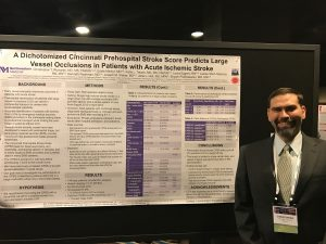 "Dr. Richards posing with his original research poster entitled ""A Dichotomized Cincinnati Prehospital Stroke Score Predicts Large Vessel Occlusions in Patients with Acute Ischemic Stroke""."